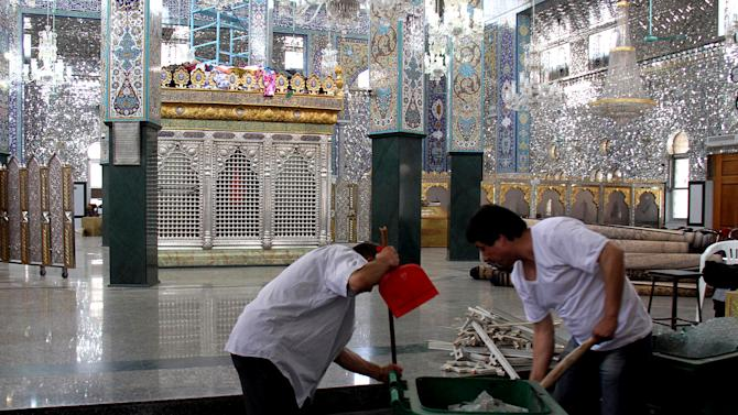 FILE - In this June 14, 2012, file photo, Syrian workers clean broken glass inside the Sayyida Zeinab shrine after a car bomb exploded near the shrine, in a suburb of Damascus, Syria. Iraqi Shiites increasingly fear the Muslim sect and its holy sites could be targeted in Syria, and Iranian-linked militants loyal to the faction are girding for a new eruption of retaliatory sectarian fighting, according to Iraqi Shiite leaders and government officials. (AP Photo/Bassem Tellawi, File)