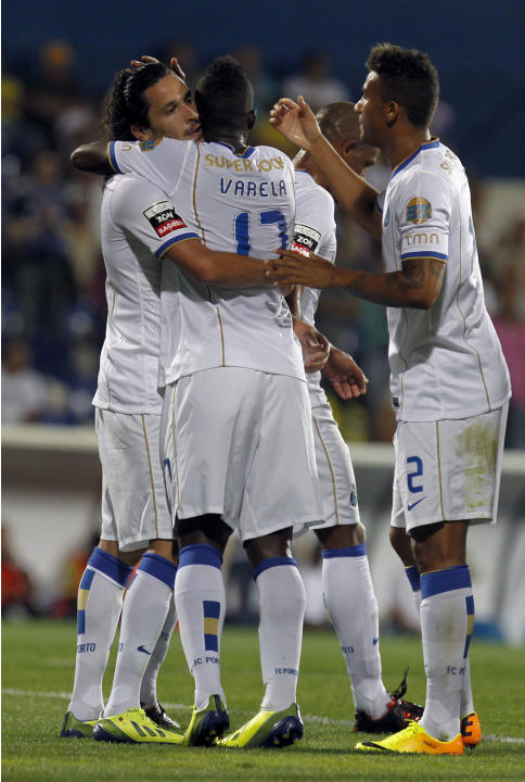 "Porto's Luis ""Lica"" Carneiro, left, celebrates with teammates Silvestre Varela, center, and Danilo Silva, from Brazil, after scoring the opening goal against Estoril during their Portuguese league soc"