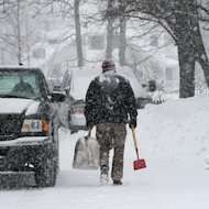 A man heads out to clear snow as it falls again, Monday, Feb. 11, 2013 in Concord, N.H. After digging out from two feet of snow over the weekend more snow arrived on Monday. (AP Photo/Jim Cole)