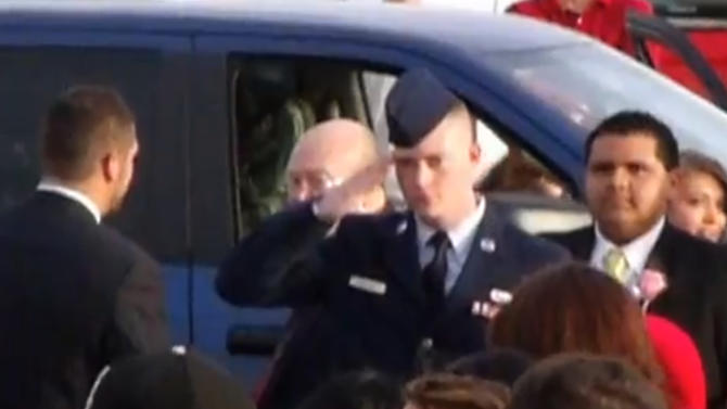 In this still image taken from an April 20, 2013 video provided by Tammy Garth, Airman Cassey Widener salutes as his sister, Courtrney Widener, arrives for prom at Liberal High School in Liberal, Kan. Courtney wanted her brother, recently returned from Afghanistan, to escort her to front door of the school, but school officials denied her request stating that at 22, he was too old to participate. The high school principal that barred Airman Cassey Widener from escorting his sister to prom has apologized, saying the intent was not to dishonor him. Deputy Superintendent Paul Larkin said Tuesday, April 30, 2013 that a policy change allowing exceptions to the age restriction will be presented at Monday's school board meeting. (AP Photo/Tammy Garth)