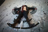 Kelli Hallett makes a snow angel in Times Square, Friday, Feb. 8, 2013, in New York. Snow began falling across the Northeast on Friday, ushering in what was predicted to be a huge, possibly historic blizzard and sending residents scurrying to stock up on food and gas up their cars. (AP Photo/John Minchillo)