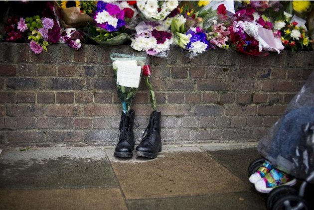 FILE - In this Friday, May 24, 2013 file photo, military boots are laid in tribute outside the Woolwich Barracks, in London, in response to the bloody attack on Wednesday when a British soldier was ki