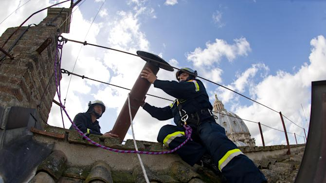 In this photo provided by the Vatican paper L'Osservatore Romano, taken on Saturday, March 9, 2013 and made available Monday, March 11, 2013, firefighters install the top of the Sistine Chapel chimney that will signal to the world that a new pope has been elected, at the Vatican. Cardinals gathered for their final day of talks Monday before the conclave to elect the next pope, amid debate over whether the Catholic Church needs more of a manager pope to clean up the Vatican or a pastoral pope who can inspire the faithful at a time of crisis. (AP Photo/L'Osservatore Romano, ho)