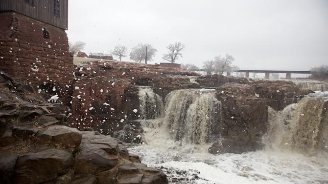 Foam is kicked up by strong wind gusts at The Falls Park in Sioux Falls, S.D., where a spring storm drove away visitors from the usually popular tourist attraction on Tuesday, April 9, 2013.  The ice storm wreaked havoc on roads, downed branches and knocked out power for thousands of residents. The National Weather Service predicted that a half-inch of ice would accumulate by day's end. Other parts of the state were grappling with large amounts of snow. (AP Photo/Amber Hunt)