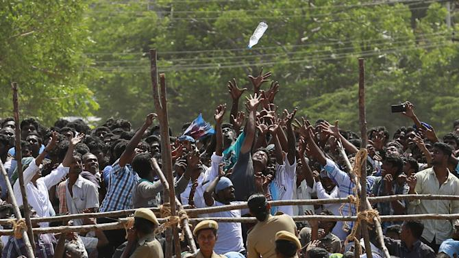 People try to catch a water bottle thrown by policemen during the funeral ceremony of former Indian President A.P.J. Abdul Kalam in Rameswaram