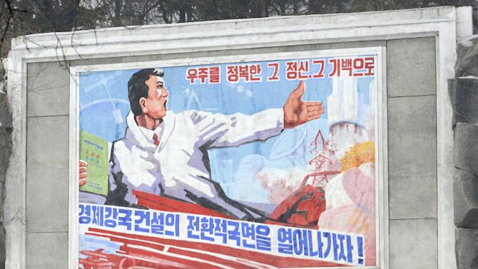 A North Korean walks past a billboard which praises the recent rocket launch success, in Pyongyang, North Korea Wednesday, Jan. 30, 2013. Last week, North Korea warned that it plans a third nuclear test to protest toughened international sanctions meant to punish it for firing a long-range rocket in December. The world sees the launch as a ballistic missile test banned by the U.N., while Pyongyang says it launched a satellite into orbit as part of a peaceful space development program. (AP Photo/Kyodo News)  JAPAN OUT, MANDATORY CREDIT, NO LICENSING IN CHINA, HONG KONG, JAPAN, SOUTH KOREA AND FRANCE