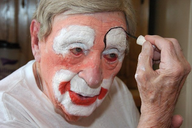 "In this March 29, 2012, photo, Floyd ""Creeky"" Creekmore puts on his makeup before a visit with children at a circus in Billings, Mont. Guinness World Records has anointed the world's oldest performing clown, and it's none other than Creekmore, a former Montana rancher who's been donning the big nose and bright makeup for almost eight decades. (AP Photo/Matthew Brown)"
