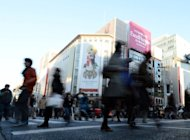 Shoppers walk in the Ginza shopping district in Tokyo on December 1. Japan says its economy shrank by 0.9 percent in the three months to September, leaving unchanged the preliminary figure amid fears the country is slipping into recession