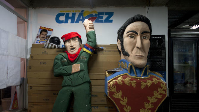Dolls of Venezuela's late President Hugo Chavez, left, and independence hero Simon Bolivar sit inside the 23 de Enero neighborhood campaign command center for the ruling United Socialist Party of Venezuela (PSUV) in Caracas, Venezuela, Friday, April 12, 2013. Nicolas Maduro, Chavez's hand-picked successor, is running for president against opposition candidate Henrique Capriles on April 14, in an election to replace Chavez who died on March 5. (AP Photo/Ramon Espinosa