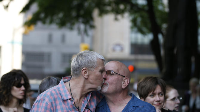 Rick Spitzborg, right, kisses his partner Blaine Bonham during a rally at City Hall, Tuesday, May 20, 2014, in Philadelphia. Pennsylvania's ban on gay marriage was overturned by a federal judge Tuesday. (AP Photo/Matt Slocum)