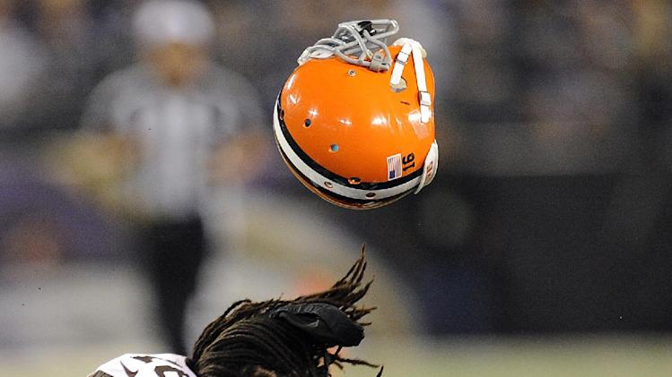 Baltimore Ravens long snapper Morgan Cox tackles Cleveland Browns wide receiver Josh Cribbs (16) as Cribbs' helmet is dislodged from a hit by another player during the first half of an NFL football game in Baltimore, Thursday, Sept. 27, 2012. (AP Photo/Nick Wass)