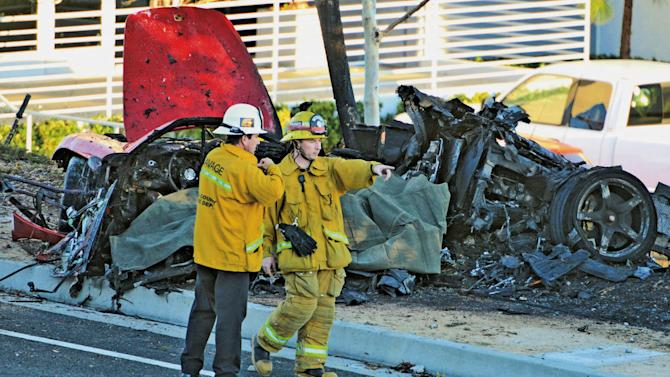 """FILE - In this Nov. 30, 2013, file photo, sheriff's deputies work near the wreckage of a Porsche that crashed into a light pole on Hercules Street near Kelly Johnson Parkway in Valencia, Calif. A coroner's report says the Porsche carrying """"Fast & Furious"""" star Paul Walker may have been going 100 mph or more before it crashed, killing both Walker and the driver. The report released Friday, Jan. 3, 2014, by the Los Angeles County coroner's office says that Roger Rodas, Walker's friend and financial adviser, was driving the 2005 Porsche Carrera GT at an unsafe speed, estimated by witnesses to be 100 mph or more. (AP Photo/The Santa Clarita Valley Signal, Dan Watson, File)"""