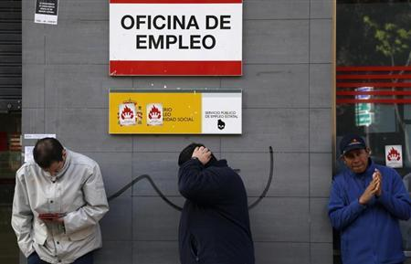 People wait in a queue to enter a government-run employment office in Madrid