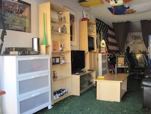 This man cave transforms a tandem garage. Two TVs are the focal points of the space. Salvaged inspirational posters, antique flags, and team jerseys enhance the spirited, rah-rah atmosphere. The Astroturf provides texture and blends in seamlessly with the wood-like furniture palette, yet juxtaposes nicely with sleeker, more artificial elements, like the neon signs and fiberglass surfboards. Not pictured: a full-size kegerator, leather couches, maps, bikes, etc. Interior design by Matt and Rob.