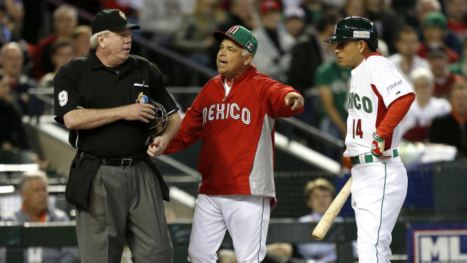 Mexico manager Rick Renteria argues a call against Eduardo Arredondo, right, with home plate umpire Brian Gorman during the sixth inning of a World Baseball Classic game against Canada, Saturday, March 9, 2013, in Phoenix. Canada won 10-3.  (AP Photo/Matt York)