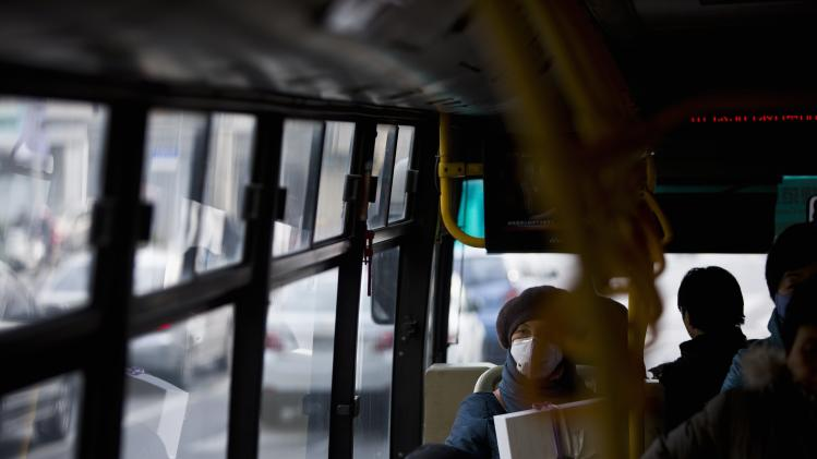 A passenger wears a mask on a public bus during a hazy day in downtown Shanghai