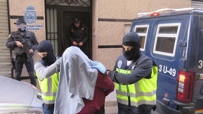 A man is led by Spanish police officers out of a building to a police car in this photo released by the Spanish Interior Ministry