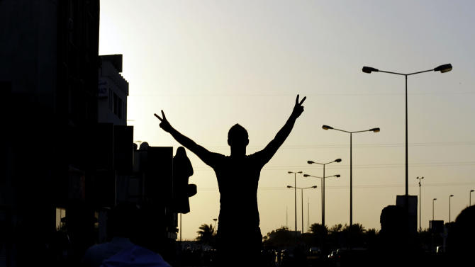 A Bahraini anti-government protester gestures toward riot police during clashes in Sitra, Bahrain, on Wednesday, Feb. 13, 2013. Clashes erupted in several opposition villages around the kingdom on the eve of the second anniversary of a pro-democracy uprising. (AP Photo/Hasan Jamali)