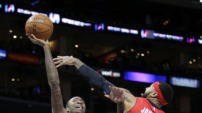 Los Angeles Clippers' Jamal Crawford, left, shoots as Toronto Raptors' James Johnson defends during the first half of an NBA basketball game Saturday, Dec. 27, 2014, in Los Angeles. (AP Photo/Jae C. Hong)