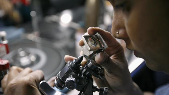 File photo of an employee checking the shape of a diamond through a magnifying glass in Surat
