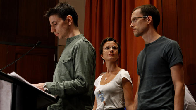 Josh Fattal, left, addresses reporters as Shane Bauer, right, holds hands with Sarah Shourd, his fiance, fellow hiker and captive, Sunday, Sept. 25, 2011 in New York. The two men were released last week after being held for espionage in an Iranian jail for almost two years. (AP Photo/Craig Ruttle)