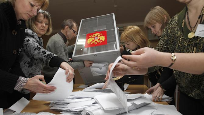 Electoral commission staff count ballot papers after voting closed at a polling station in the town of Smolensk, western Russia, Sunday, March 4, 2012. Prime Minister Vladimir Putin won Russia's presidential election on Sunday, according to exit polls cited by state television, but the vote was tainted by widespread violations claimed by the opposition and independent observers. (AP Photo/Sergei Grits)
