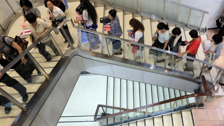 Shoppers make a line on the stairs for a cashier at a department store in Tokyo Friday, June 28, 2013. Japan got a dose of upbeat economic news Friday when the government said industrial production rose 2 percent in May from April, the fourth straight monthly increase, while the most-watched consumer price index stopped falling for the first time in seven months. (AP Photo/Itsuo Inouye)