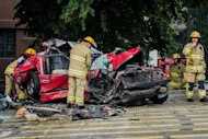 Firefighters inspect a taxi crushed during an accident with two double-decker buses in Hong Kong on November 19, 2012. The taxi driver and two passengers, who have been identified as chefs working for top British chef Heston Blumenthal, were killed in the accident