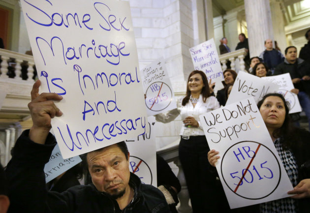 Carlos Perez, of Providence, R.I., left, displays a placard as he joins with other demonstrators opposed to same-sex marriage during a rally at the Statehouse, in Providence, Tuesday, Jan. 15, 2013. The Rhode Island House Judiciary Committee began hearing testimony from supporters and opponents of same-sex marriage Tuesday. (AP Photo/Steven Senne)