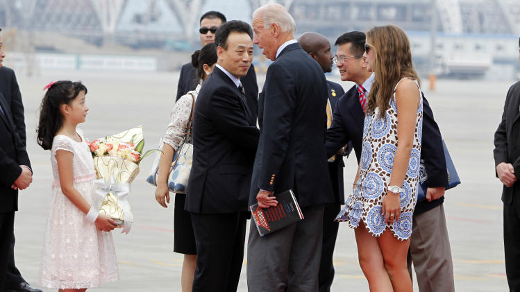 U.S. Vice President Joe Biden, center, reacts as he is presented with flowers after he arrived onboard the Air Force Two at the airport in Chengdu, China, Saturday, Aug. 20, 2011. (AP Photo/Ng Han Guan, POOL)
