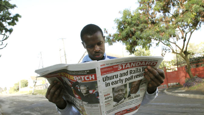 A Kenyan looks at a newspaper a day after the country's presidential election, at a roadside stall in Nairobi, Kenya Tuesday, March 5, 2013.  Kenya's presidential election drew millions of eager voters who endured long lines to cast ballots Monday, but the vote was marred by violence that left 19 people dead, including four policemen hacked to death by machete-wielding separatists. (AP Photo/Sayyid Azim)
