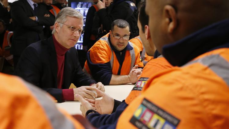 Belgium's King Philippe listens to garbage collectors during a visit to a depot of Brussels' garbage collection and recycling service