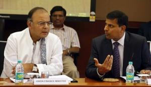 India's new Finance Minister and Defence Minister Arun Jaitley listens to Reserve Bank of India Governor Raghuram Rajan during a financial stability development council meeting in Mumbai