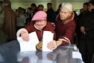 Two Lithuanian women cast their ballot at a polling station in Vilnius. Lithuania's left-wing and populist opposition parties have moved to form a new government after austerity-weary voters evicted the Baltic state's Conservative-led coalition in a general election