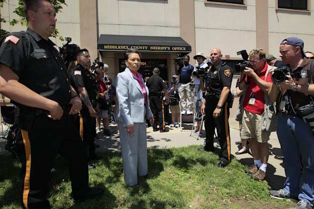 Middlesex County sheriff Mildred S. Scott, center, stands with officers and the media outside the sheriff's office in New Brunswick, N.J., Thursday, May 31, 2012, as they wait for the arrival of Dharu