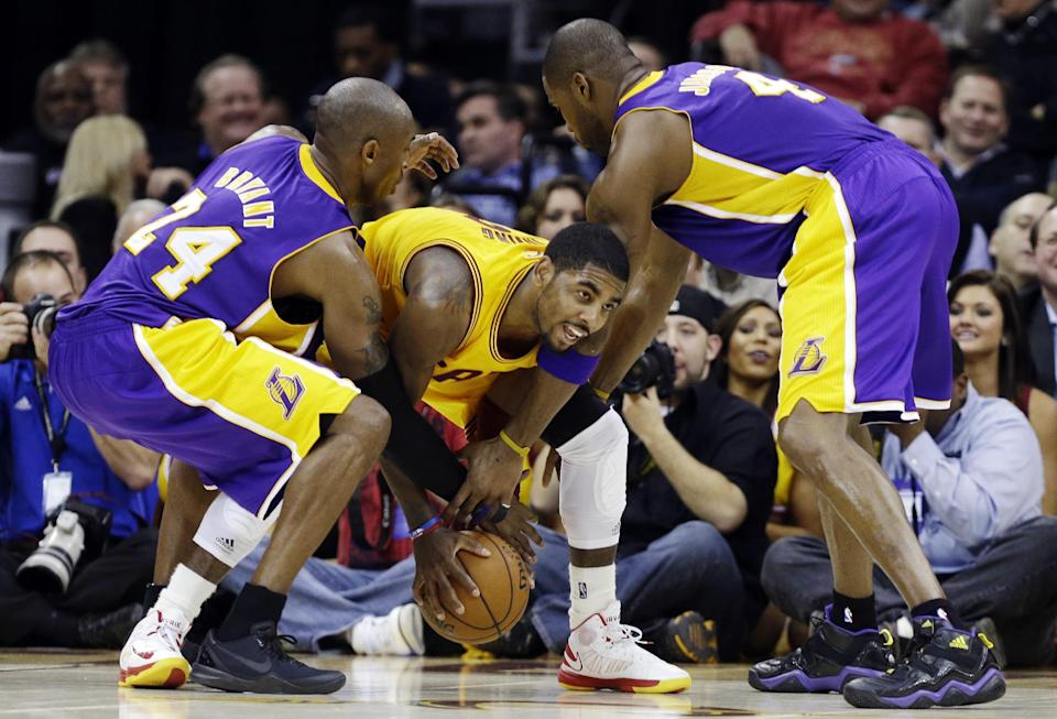 Los Angeles Lakers' Kobe Bryant, left, and Antawn Jamison, right, tries to wrestle the ball away from Cleveland Cavaliers' Kyrie Irving in the fourth quarter of an NBA basketball game, Tuesday, Dec. 11, 2012, in Cleveland. The Cavaliers won 100-94. (AP Photo/Mark Duncan)