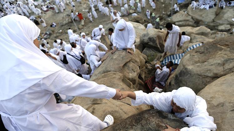 Muslim pilgrims climb a rocky hill called the Mountain of Mercy on the Plain of Arafat near the holy city of Mecca, Saudi Arabia, Thursday, Oct. 25, 2012. Saudi authorities say around 3.4 million pilgrims — some 1.7 million of them from abroad — have arrived in the holy cities of Mecca and Medina for this year's pilgrimage. (AP Photo/Hassan Ammar)