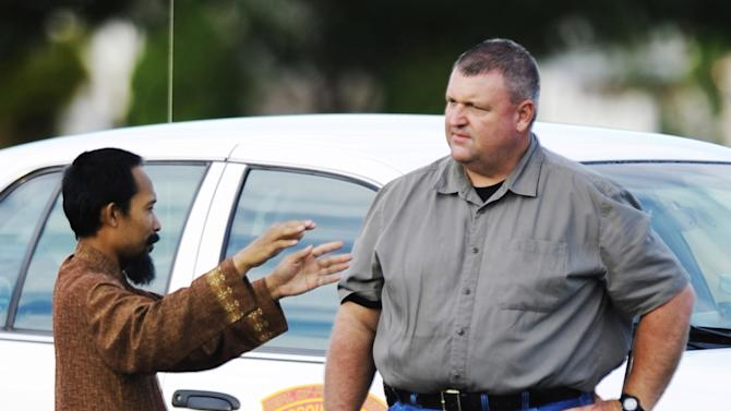 Imam Lahmuddin, left, speaks with an investigator outside the Islamic Society of Joplin, Mo., mosque, after a fire destroyed the building, Monday, Aug. 6, 2012, in Joplin, Mo. The fire was the second fire to hit the Islamic center in little more than a month. (AP Photo/The Joplin Globe, T. Rob Brown) MANDATORY CREDIT