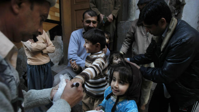 """In this Feb. 9, 2014 photo, Pakistani health workers vaccinate children against polio, in Peshawar, Pakistan. Pakistan's beleaguered battle to eradicate polio is threatening a global, multi- billion dollar campaign to wipe out the disease worldwide. Because of Pakistan, the virus is spreading to countries that were previously polio free, say U.N. officials. """"The largest poliovirus reservoir of the world,"""" is in Peshawar, the capital of Pakistan's northwest Khyber Pukhtunkhwa province, which borders Afghanistan, according to the World Health Organization. (AP Photo/Mohammad Sajjad)"""