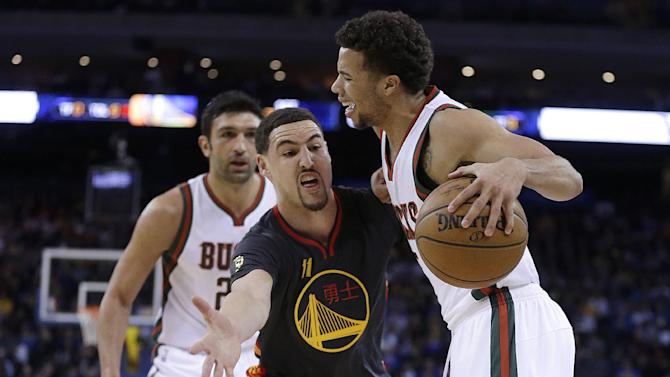 Milwaukee Bucks' Michael Carter-Williams, right, drives the ball against Golden State Warriors' Klay Thompson, center, as Bucks' Zaza Pachulia, left, watches during the first half of an NBA basketball game Wednesday, March 4, 2015, in Oakland, Calif. (AP Photo/Ben Margot)