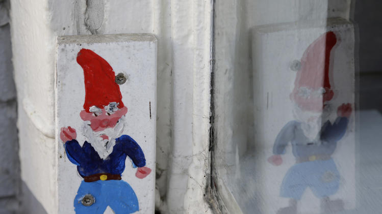 A hand-painted gnome is shown on a window outside the Haddon Hill Cafe Tuesday, Jan. 29, 2013 in Oakland, Calif. Small paintings of gnomes that have popped up on utility poles have become a community sensation in Oakland, prompting Pacific Gas & Electric Co. to say Tuesday that it will keep them in place for now. The portraits on 6-inch blocks of wood began going up last year in an apparent effort to brighten up the blue-collar California city. There are currently more than 2,000 of the images on utility poles, with many screwed to the bases. (AP Photo/Eric Risberg)
