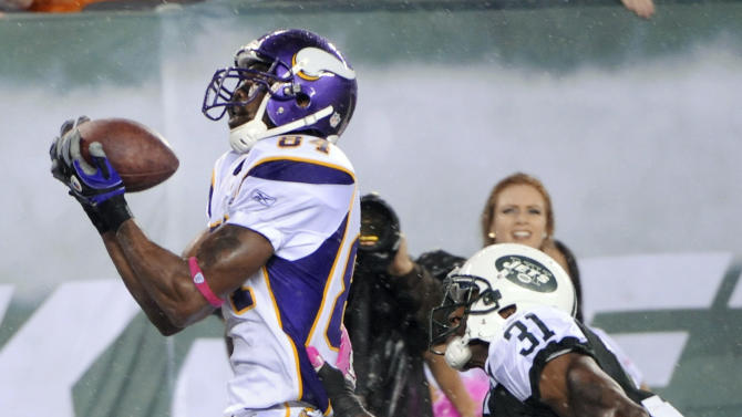 FILE - This Oct. 11, 2010, file photo shows Minnesota Vikings' Randy Moss catching a touchdown pass while covered by New York Jets' Antonio Cromartie during the third quarter of an NFL football game, in East Rutherford, N.J. Moss is calling it a career after 13 seasons in the NFL as one of the most dynamic and polarizing players the league has ever seen.  (AP Photo/Bill Kostroun, File)