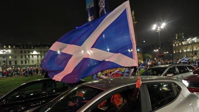 A passenger in a car waves a Scottish Saltire flag from the window in central Glasgow