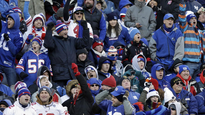 FILE - In this Dec. 30, 2012, file photo, New York Giants fans cheer during the second half of an NFL football game against the the Philadelphia Eagles in East Rutherford, N.J. Just over a year before the New York area hosts the Super Bowl, the temperature was in the teens. With an outdoor game in a cold-weather state, the NFL will be at the mercy of Mother Nature for the 2014 championship. (AP Photo/Kathy Willens)