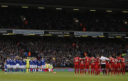 Oldham Athletic players and Liverpool players stand during a minute's silence in honour of former Oldham Athletic and Liverpool player Wayne Harrison and Portuguese great Eusebio during their FA C