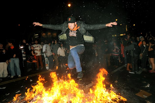 A San Francisco Giants fan jumps over a bonfire in San Francisco&#39;s Mission district Sunday, Oct. 28, 2012, after the Giants swept the Detroit Tigers to win baseball&#39;s World Series. (AP Photo/Noah Berger)