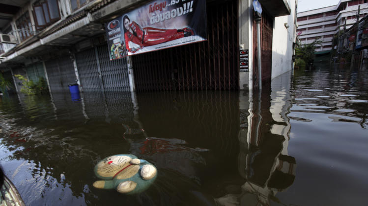 A stuffed doll of Doraemon, a famous Japanese cartoon character, floats over water at a flooded neighborhood in Bangkok, Thailand, Sunday, Oct. 30, 2011. City dikes overflowed in at least two places as coastal high tides pushed up the main Chao Praya river from the Gulf of Thailand, with water spilling into streets as city workers and troops shored up concrete walls with sandbags. (AP Photo/Altaf Qadri)