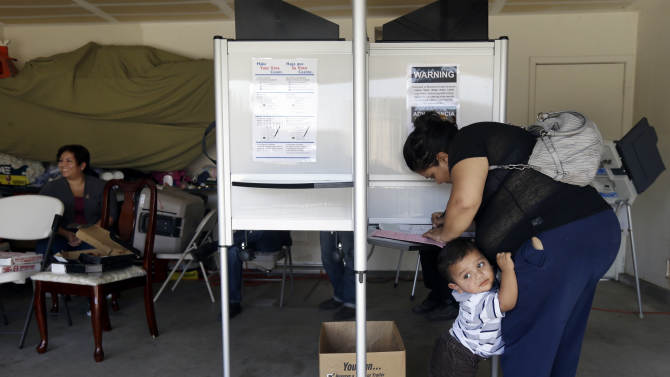 Yesenia Perez marks her ballot as her 1-year-old Eduardo Sanchez clings to her in the Weston Ranch area of Stockton, Calif. on Tuesday, Nov.  6, 2012. The neighborhood was heavily affected by foreclosures in the past few years. Perez, 34, a mother of five who works at a local fruit-packing house, has had her share of hard times. After both she and her husband had their work hours cut amid the sputtering economy, they lost their home to foreclosure three years ago. Yet on Tuesday, she felt compelled to do something she had never done before: vote. (AP Photo/Marcio Jose Sanchez)