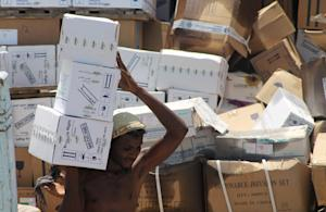 A Yemeni man unloads medical aid boxes from a boat…