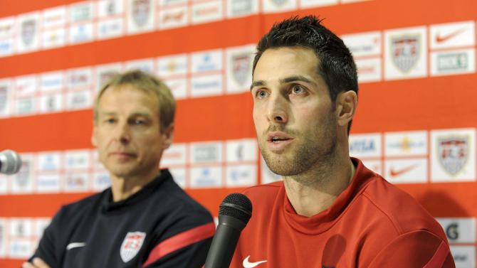 FILE - In this Feb. 28, 2012 file photo,U.S. soccer team defender Carlos Bocanegra answers a question during a press conference prior to a training session ahead of their friendly soccer match against Italy in Genoa, ItalyAt left is U.S. soccer team German coach Jurgen Klinsmann. U.S. captain Bocanegra has been dropped from the roster for World Cup qualifiers against Costa Rica and Mexico. (AP Photo/Tanopress, File)